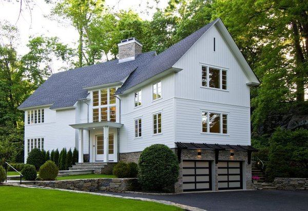 The modern barn style is defined by the vertical and horizontal siding patterns that emulate the feel of a classic New England Barn. The locally sourced stone is very natural and harkens to traditional stone foundations of the area.  Modern touches include sleek trim detailing, clean lines in the windows, frosted glass paneled garage doors and dark stained wood awning over the garage. Photo  of Greenwich Modern Barn modern home