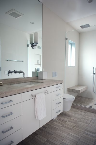Master bath features matched honed marble surfaces on vanity top, floor, shower floor, and bench. Walls and shower ceiling are surfaced in large format porcelain tile. Wall hung vanity is custom. Photo 16 of Golden Gate Park Residence modern home