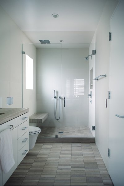 The size of the master bath was increased during the renovation. The windowpane in the shower is sandblasted for privacy. The shower features traditional shower head; hand held shower; and rain shower above bench. Photo 17 of Golden Gate Park Residence modern home