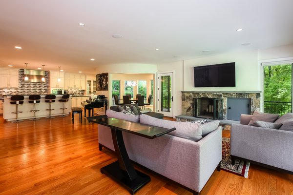 Modern home with medium hardwood floor, ceramic tile backsplashe, refrigerator, white cabinet, ceiling lighting, recessed lighting, microwave, wall oven, dishwasher, range, wine cooler, drop in sink, range hood, living room, and wood burning fireplace. Living Area Photo 3 of Asian Contemporary
