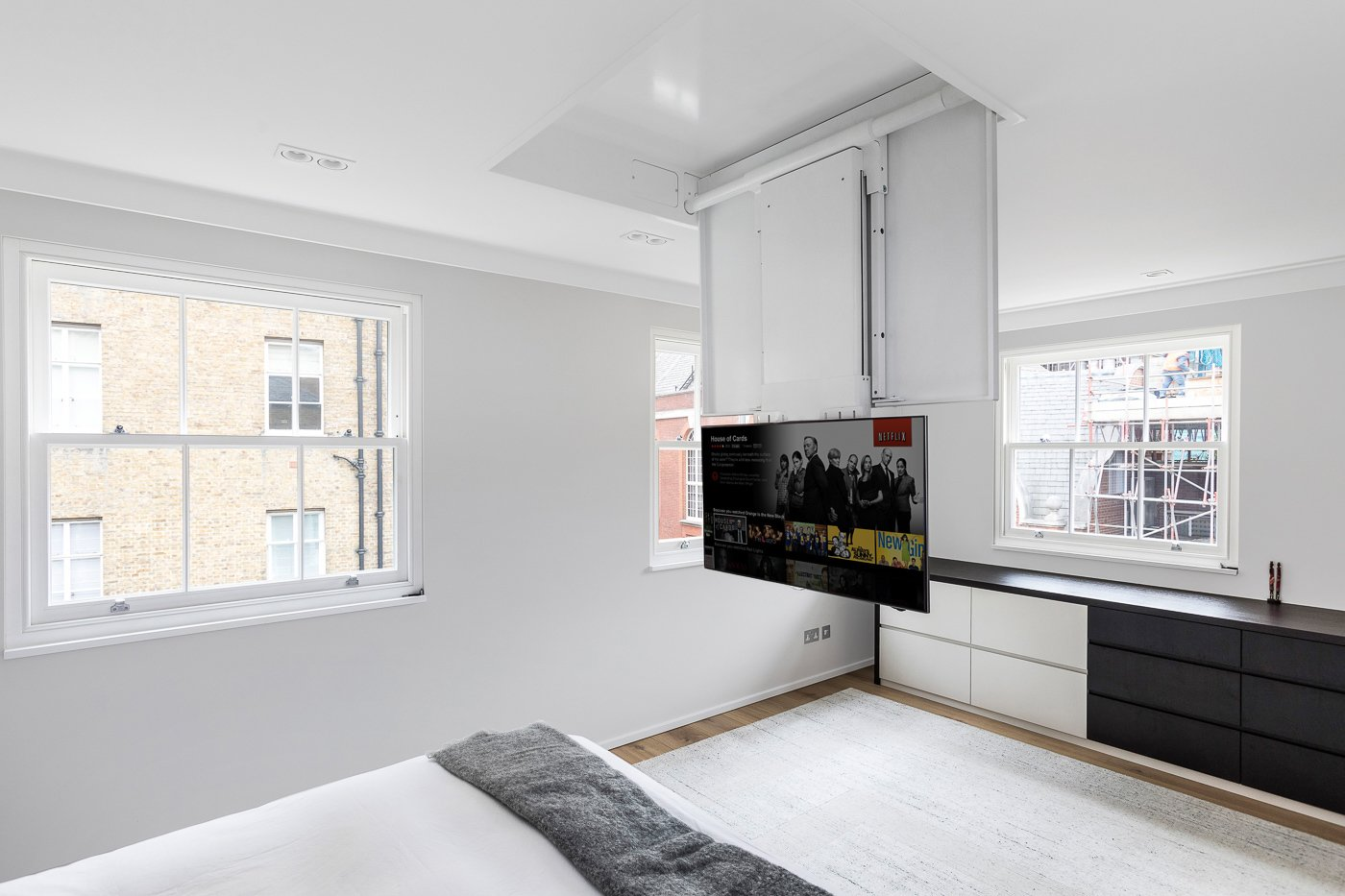 Motorised TV lift in the master bedroom Tagged: Bedroom, Bed, Ceiling Lighting, and Medium Hardwood Floor.  Best Photos from Regent's Park Townhouse