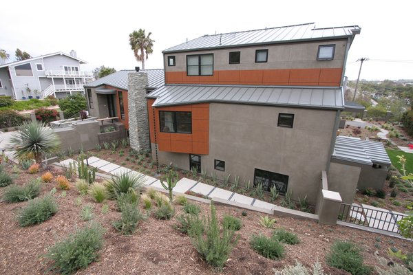 Drought tolerant and native landscaping for water-consciousness in the drought-prone area of San Diego. A rain chain is visible to the right of the chimney. Photo  of The Jaska Nolan Residence modern home
