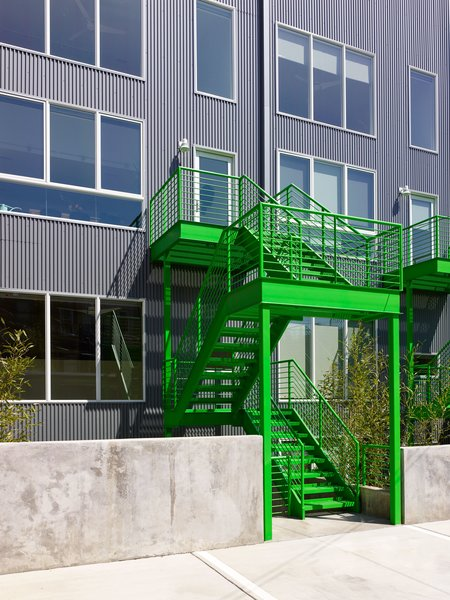 Rear exterior with corrugated metal and bright green railings. Photo 5 of 10th Street Duplexes modern home
