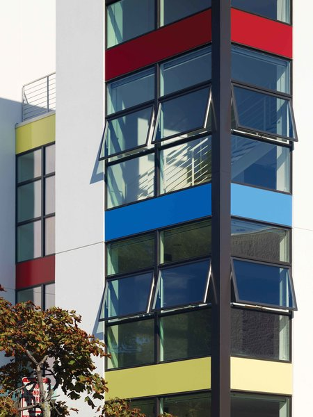 Brightly colored aluminum panels draw passersby in while corner-wrapping windows give residents a feeling of openness and sense of eyes on the community. Photo  of Bailey Lofts modern home