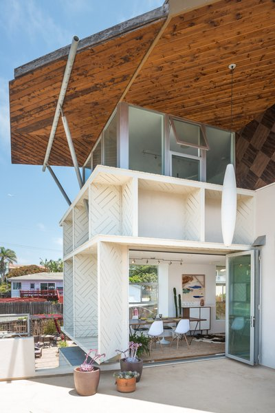 The main dining area's accordion door opens up to the balcony with an ocean view and salty breeze. Above the dining space sits the 3rd story home office with 180 degree views.  Photo  of The Beach House modern home