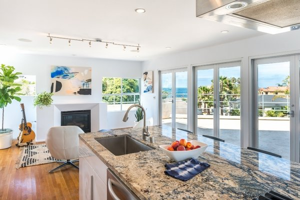 Kitchen Island work station overlooks the living room with fireplace, expansive balcony with ocean views, and the dining and bar areas that overlook the backyard (out of frame).  Photo 2 of The Beach House modern home