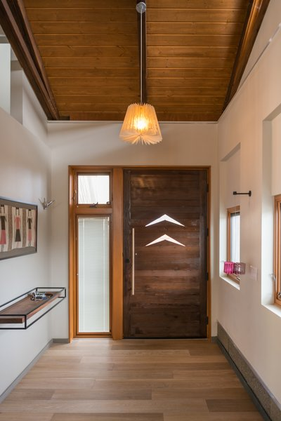 The front door was created with recycled wood beams from the original home, accented with the same boomerang cut-outs from exterior copper canopy. To maximize open floor space, Curtis Micklish designed this floating shelf to catch keys and mail and the occasional tiny toy.  Photo 5 of The Modern Mission modern home