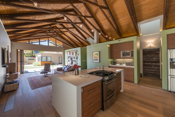 Overhead trusses made from recycled wood beams from the original home support a dramatic 16 foot ceiling. To keep the line of site wide open, an overhead hood was swapped out for a Jenn-air downdraft gas range. Photo 7 of The Modern Mission modern home