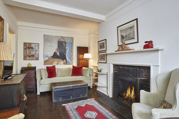 Modern home with living room, sofa, chair, floor lighting, dark hardwood floor, and wood burning fireplace. 10 Mitchell Place, Midtown East - $495,000  Located in a discreet private enclave off 49th Street, 10 Mitchell Place is a charming pre-war building with 24/7 doorman and live-in super. Apartment 9F comprises: sunny living room, 1 bedroom with updated bath, and numerous closets. There are many pre-war details: original mantlepiece, beamed ceilings, and hardwood floors. Sunny open sky views north add to the appeal of this apartment. There is a kitchen would could excel with updating; bike room and laundry. Photo 5 of Five Fabulous NYC Homes For Under $500K