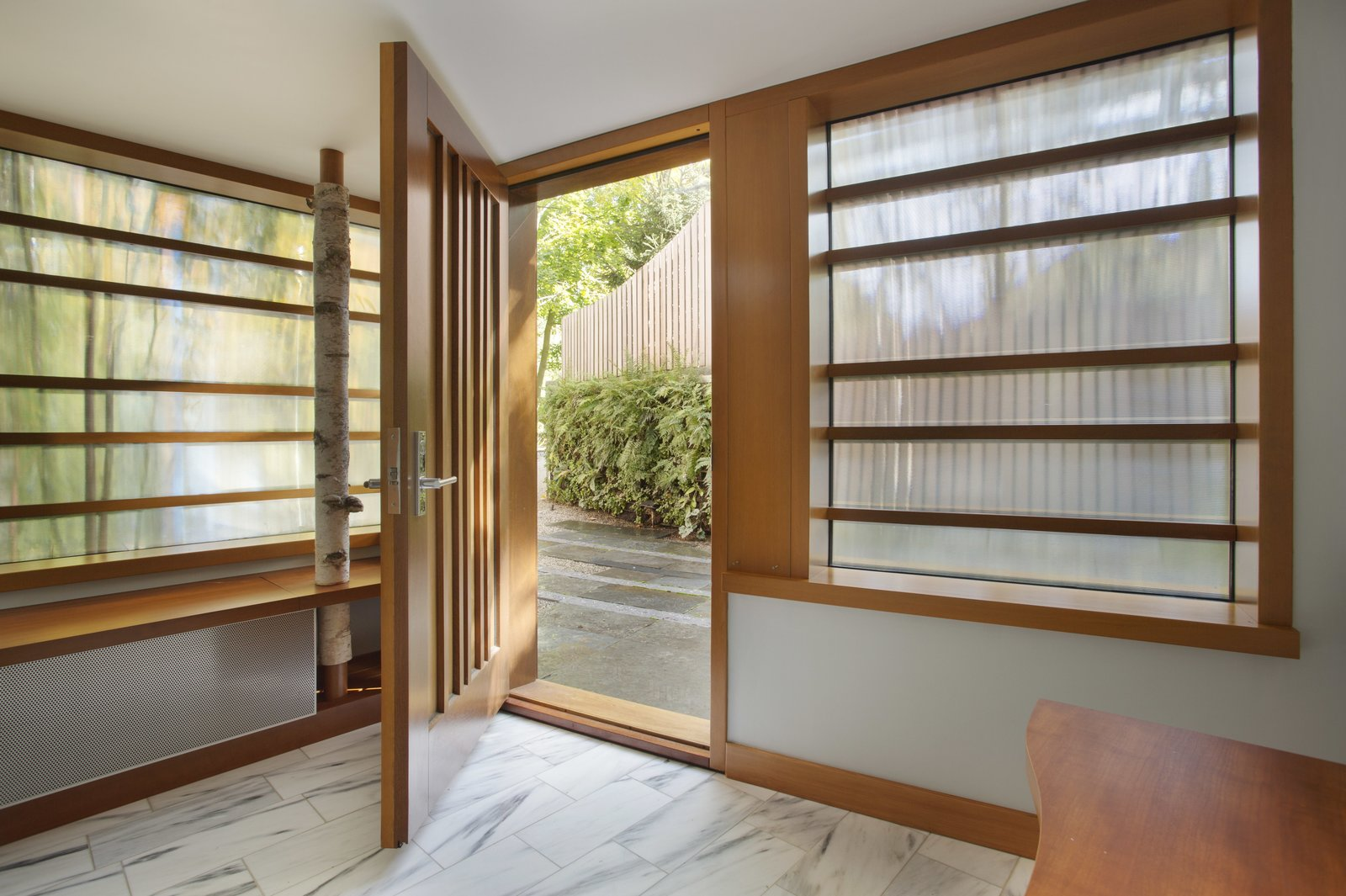 The entrance vestibule, with birch bark column and marble flooring. Sustainable Urban Villa by Wolf Architects, Inc.