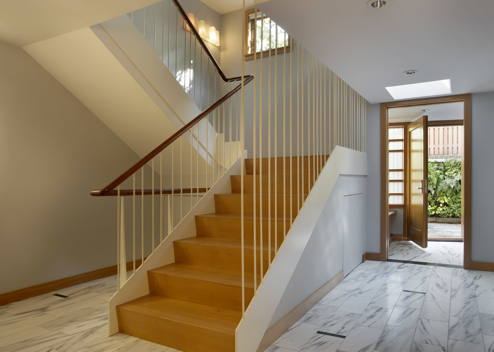 The stair of reclaimed heart pine risers and treads and a cherry railing, between irregularly spaced steel rods.  Sustainable Urban Villa by Wolf Architects, Inc.