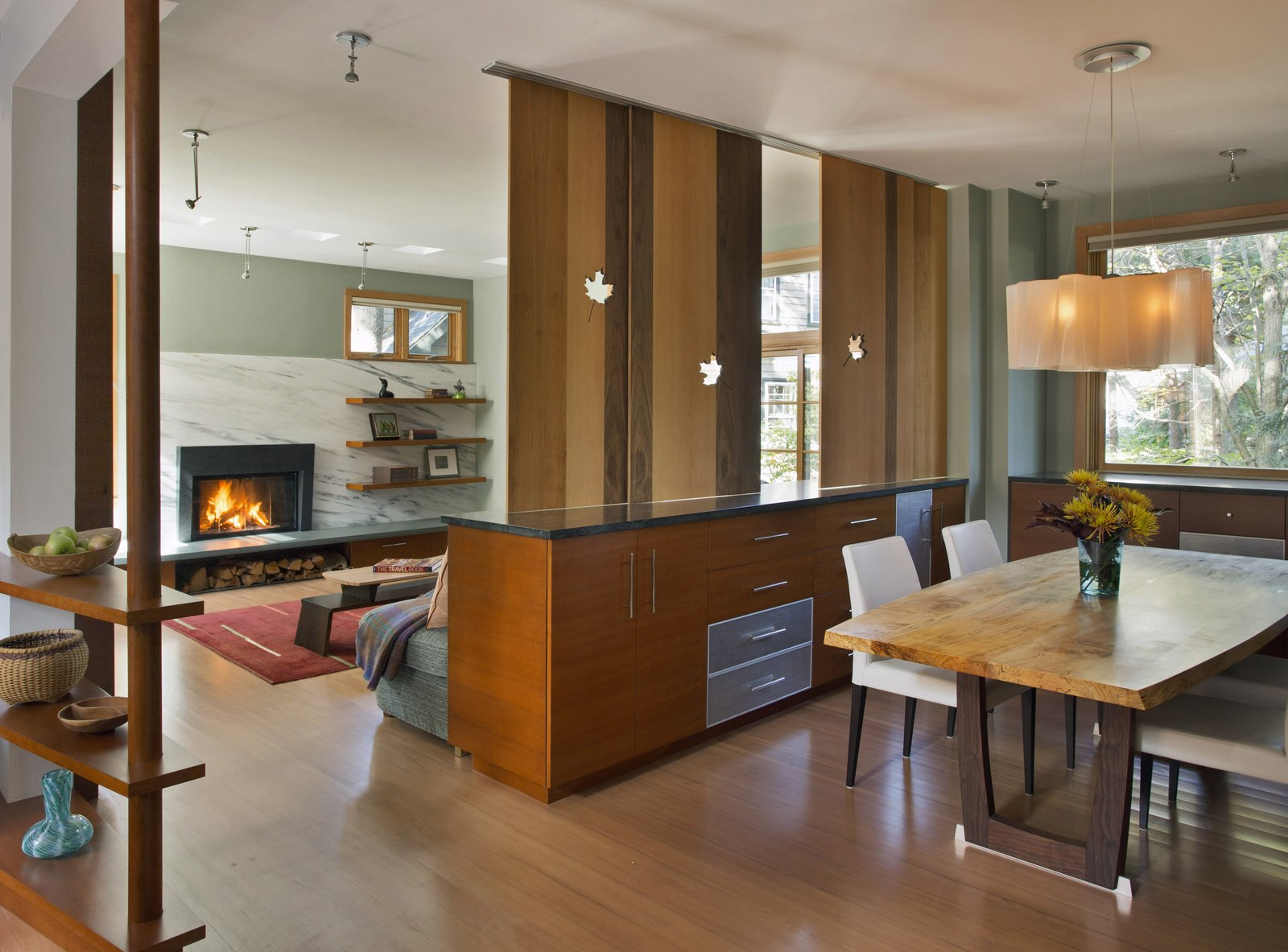 Sliding screens of veneer with leaf cut-outs between the dining room and living room.  Sustainable Urban Villa by Wolf Architects, Inc.
