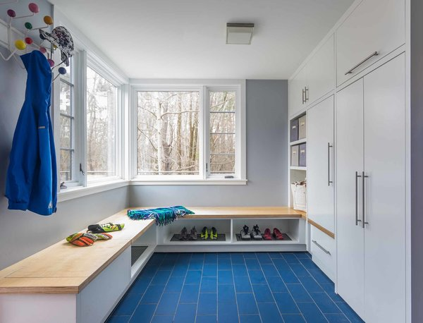 Maple veneer ApplePly tops this bench in the new mudroom, which provides boot and shoe storage/drainage, while other cabinets conceal a variety of storage spaces.