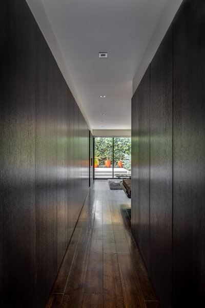 Modern home with hallway and dark hardwood floor. Panels Covering Closets and Storage - Master Suite - Rift-cut white oak, full-height, honeycomb panels and doors: hand wire brushed, stained, sealed, sanded, glazed, sanded and top-coate Photo 4 of Castro Residence