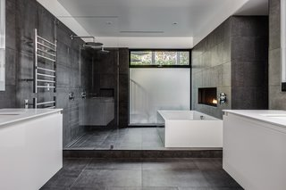 A Guide to Ceramic Versus Porcelain Tile - Photo 3 of 10 - In this master bathroom, which is complete with a soaking tub, a linear fireplace, and floating vanities, the floor and walls are covered with large-format Italian porcelain tile from Emil Ceramica.