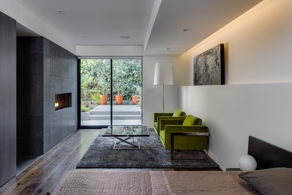 Master Suite - linear fireplace w/ lava stone in sitting area - Chairs: Thayer-Coggin, designed by Milo Baughman (new), Coffee table: vintage Thayer Coggin designed by Milo Baughman (chrome and smoke glass), bed: Alias