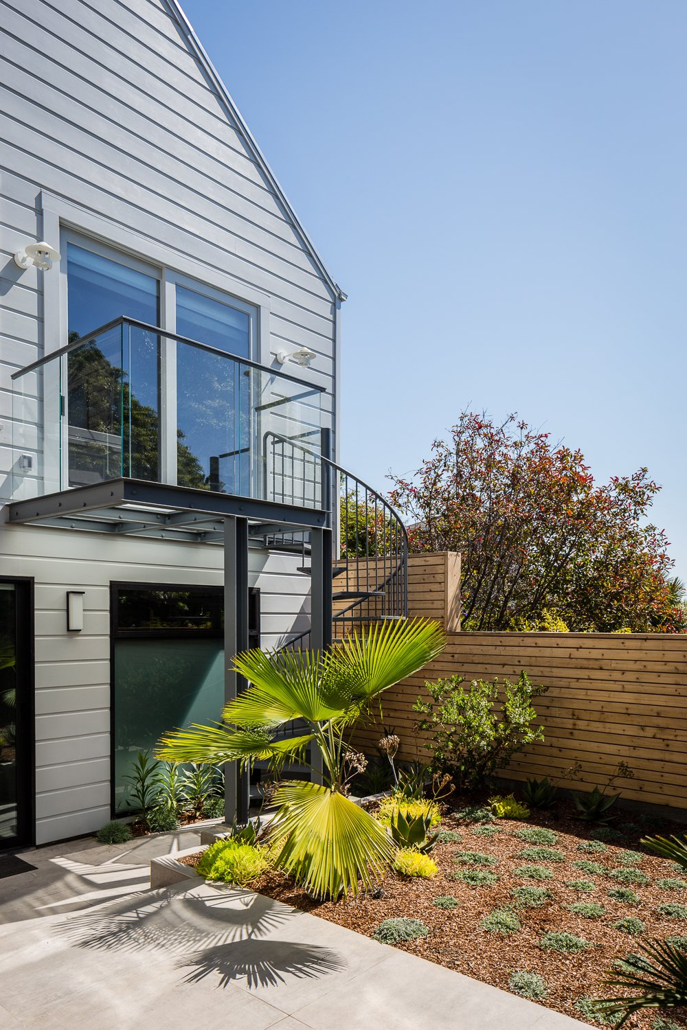 Backyard + Spiral Stairs + GlasBackyard + Spiral Stairs + Glass Deck - Large-format Italian porcelain tile from Emil Ceramica, Custom steel and glass deck. Glass decking and railings by Paige Glass, Plantings & planters by Flora Grubb Gardens, Louis Poulsen sconces