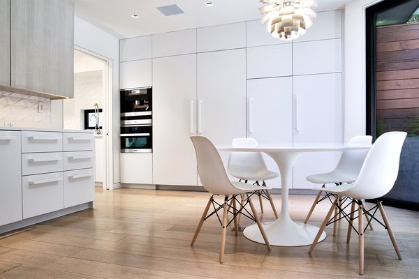 Modern home with dining room, chair, table, pendant lighting, and medium hardwood floor. Breakfast Room - Saarinen Tulip Table, Eames side chairs, Miele appliances, Louis Poulsen PH Stainless Steel Artichoke light Photo 12 of Lyon Residence