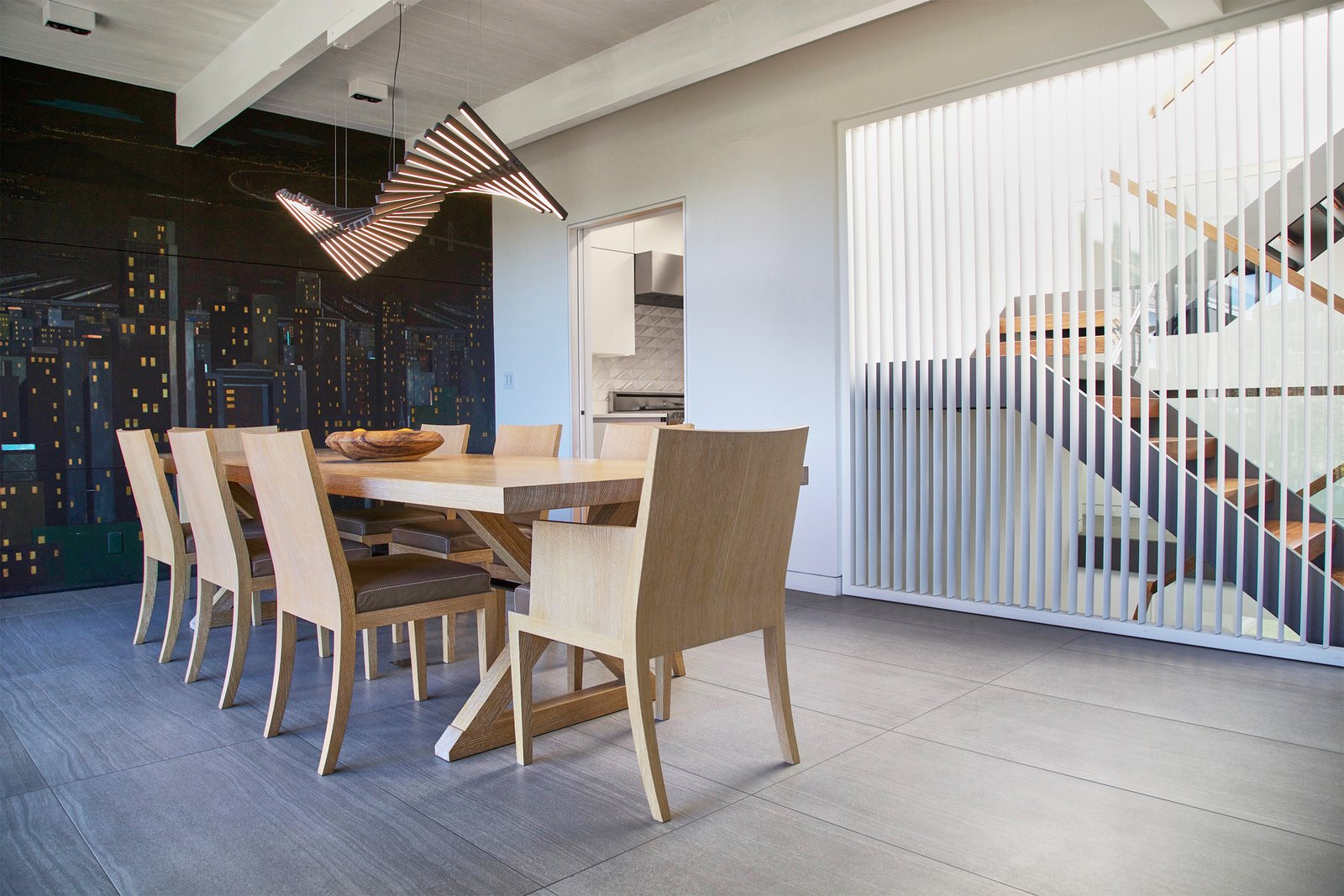 Dining Room - operable louvers at stair, original Jose Moya del Pino cityscape mural, Vibia Rythm light, Hermés table and chairs Tagged: Dining Room, Chair, Table, Ceramic Tile Floor, Accent Lighting, and Track Lighting.  Lyon Residence by Diego Pacheco Design Practice