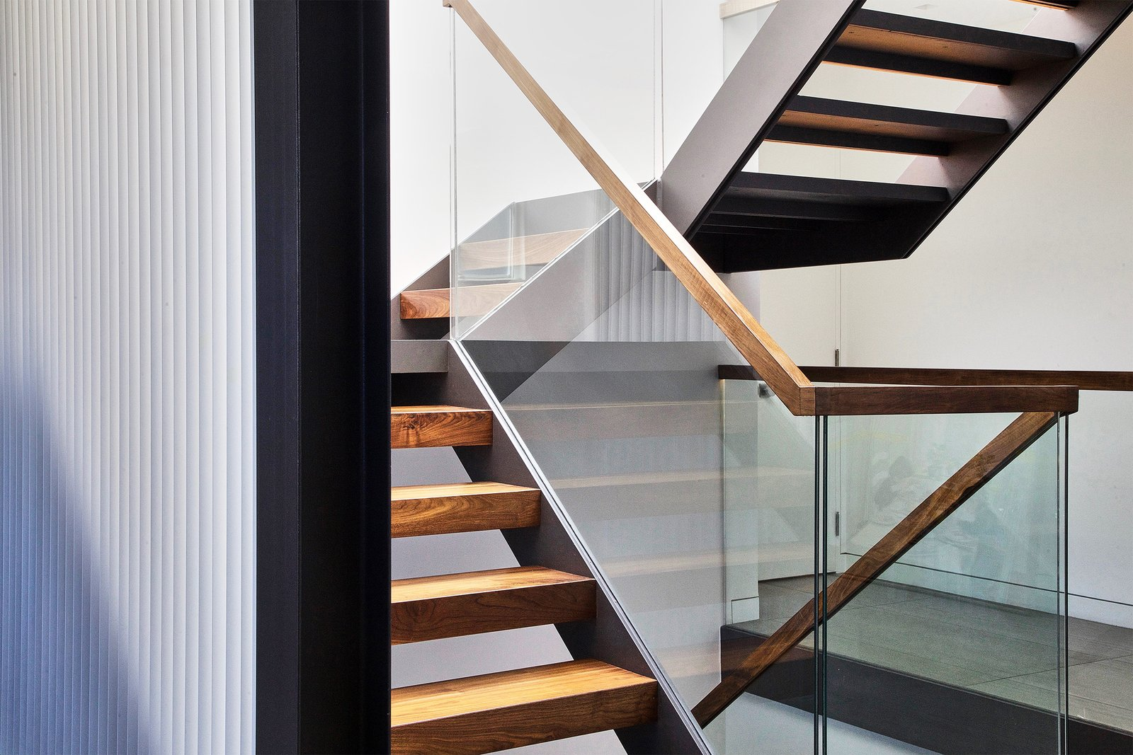Walnut and Steel stair connecting all floors Tagged: Staircase, Wood Tread, Wood Railing, and Glass Railing.  Lyon Residence by Diego Pacheco Design Practice