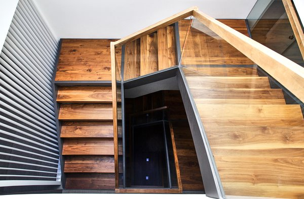 Modern home with staircase, wood railing, wood tread, and glass railing. Walnut and Steel stair connecting all floors Photo  of Lyon Residence