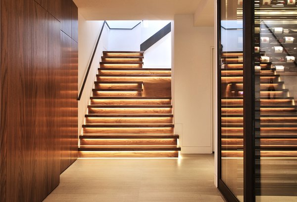 Modern home with staircase, wood tread, and wood railing. Cascading Walnut Stairs w/ LED lights Photo 13 of Lyon Residence