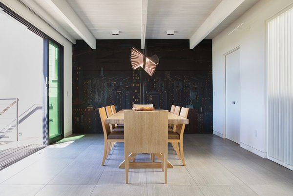 Modern home with dining room, track lighting, table, chair, accent lighting, and ceramic tile floor. Dining Room - operable louvers at stair, original Jose Moya del Pino cityscape mural, Vibia Rythm light, Hermés table and chairs, Fleetwood sliding doors to deck Photo 10 of Lyon Residence