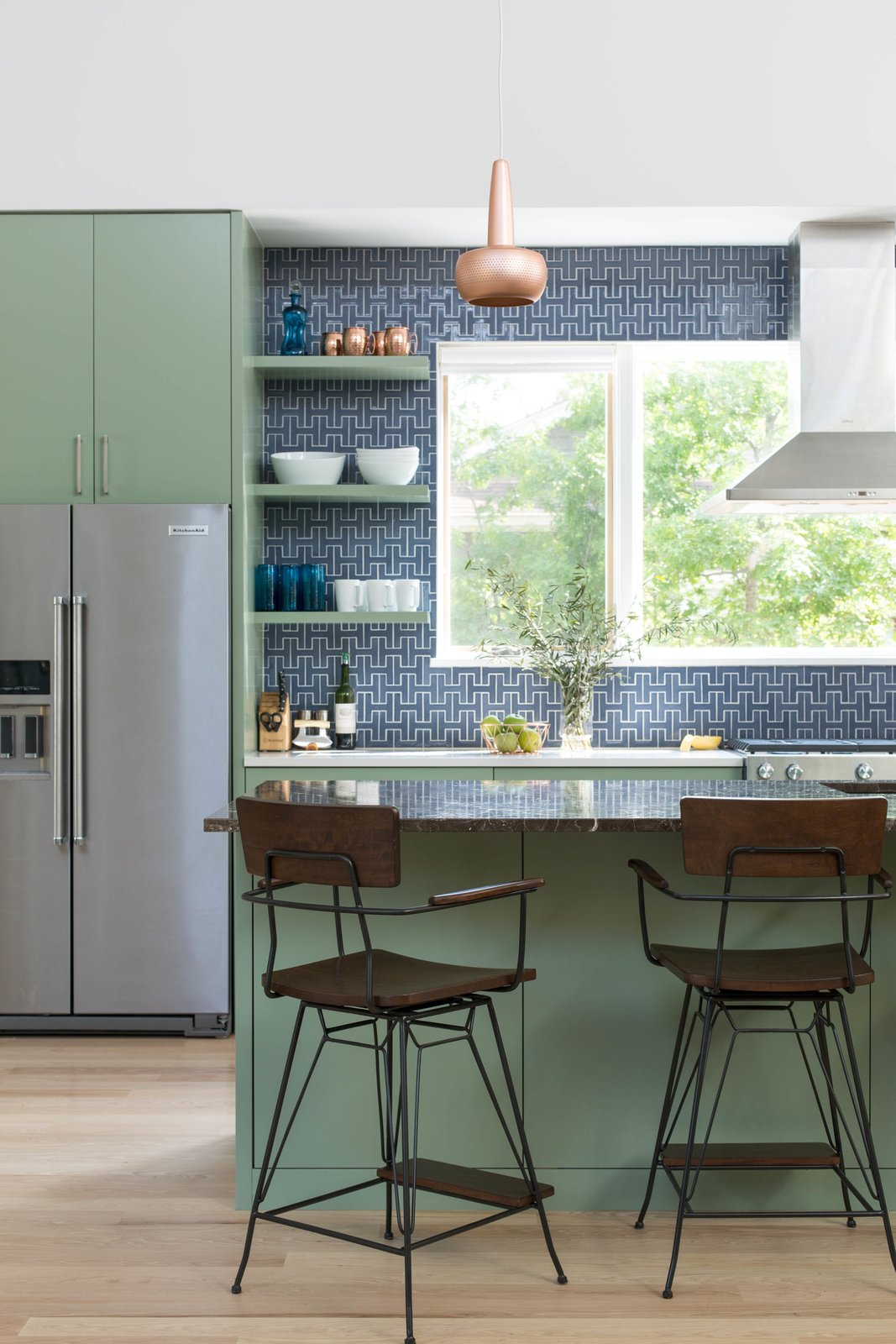 The Architect selected a recycled Fireclay Tile in Slate Blue and paired that with High Park paint from Benjamin Moore. Copper pendants from VITA accent the space. The vent hood is mounted in front of a large window, bringing in natural light and allowing for a view of the herb garden.