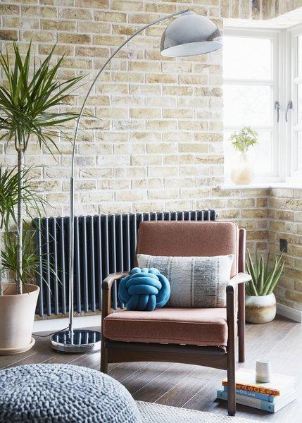 A vintage Danish teak armchair sits against a London stocks brick wall.
