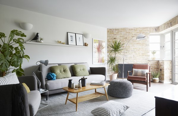 The light-filled living room, with a London stocks brick wall, vintage mid century furnishings and modern Scandi decorative touches.
