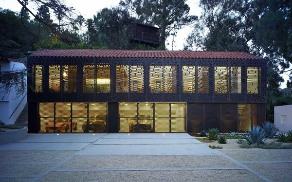 A new two-story building, consisting of a garage on its first level and a private library on the second level, includes storage, a reading area and a powder room. The illuminated facade is made of bronze-anodized aluminum metal panels. Photo  of Morgan Phoa Library and Residence modern home