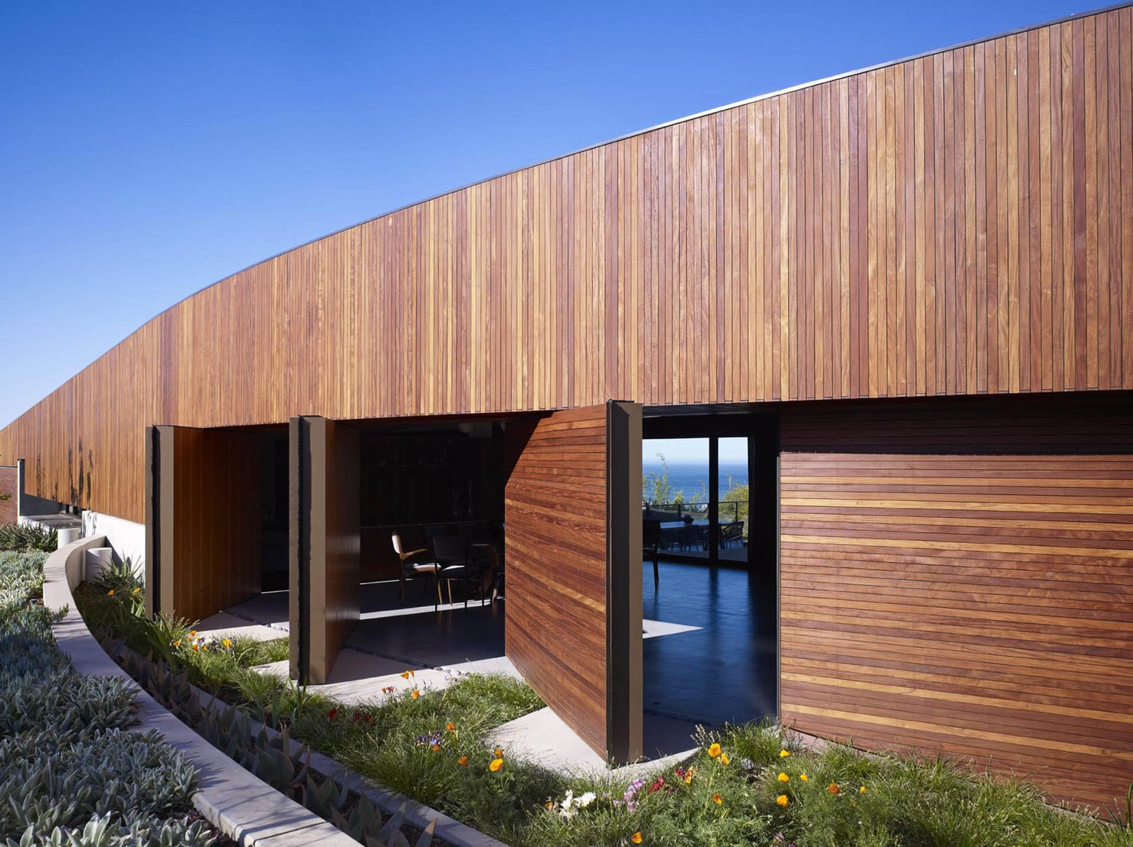 The front door and pivoting wall panels transform this façade when opened, presenting views of the interior, the courtyard and the ocean beyond.  Ziering Residence by Studio Pali Fekete architects