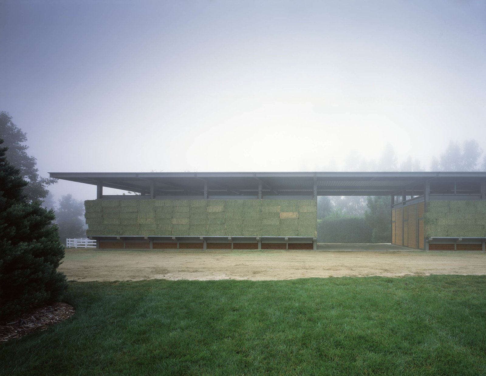 The concept is based on the ever-changing color and positioning of the hay as cladding on the barn. When hay is stacked along the outer storage shelves in the winter, it is green; as the season unfolds, the hay turns yellow, and the caretaker removes it from the shelves as it is used for feed.  Somis Hay Barn by Studio Pali Fekete architects