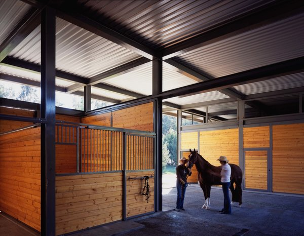 The steel structural system is designed based on a simple grid, constructed to the ideal dimensions for a horse stable. Natural ventilation is encouraged via open clearstories, and the large roof overhang protects the cladding from the rain. Photo 5 of Somis Hay Barn modern home