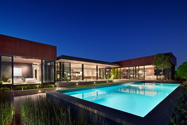 The design forms a C-shaped box that wraps around creating a courtyard. To enclose the central public space of the home, a glass pavilion has been inserted within the courtyard. Photo  of Nightingale Residence modern home