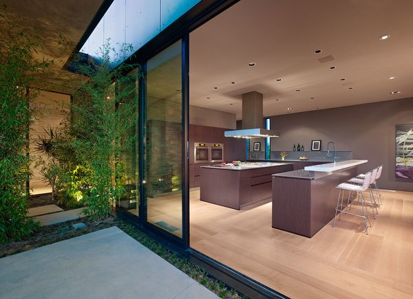 Standard black anodized aluminum sliding window and door systems optimize the flow of natural sunlight, and air through the plan's open spaces. Photo 3 of Nightingale Residence modern home