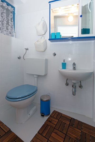 Floor decking instead of a rug gives this tiny bathroom a spa feel. Photo 13 of Shabby Chic Beach Cottage modern home