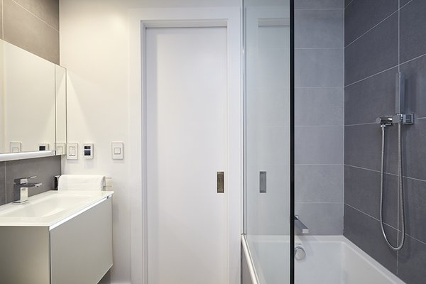 Modern home with bath room, medium hardwood floor, wall mount sink, soaking tub, alcove tub, ceiling lighting, open shower, accent lighting, one piece toilet, wall lighting, and porcelain tile wall. Photo 3 of White on White Apartment