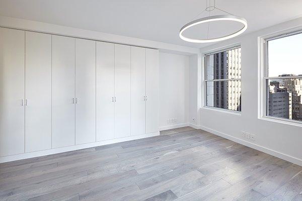 Modern home with living room, pendant lighting, and medium hardwood floor. Photo 9 of White on White Apartment
