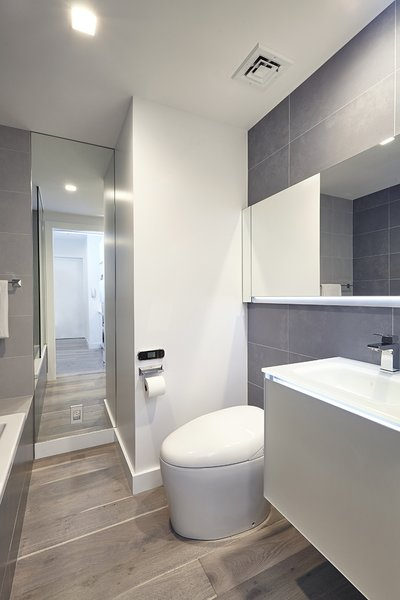 Modern home with bath room, medium hardwood floor, wall mount sink, ceiling lighting, accent lighting, recessed lighting, alcove tub, soaking tub, porcelain tile wall, and one piece toilet. Photo  of White on White Apartment