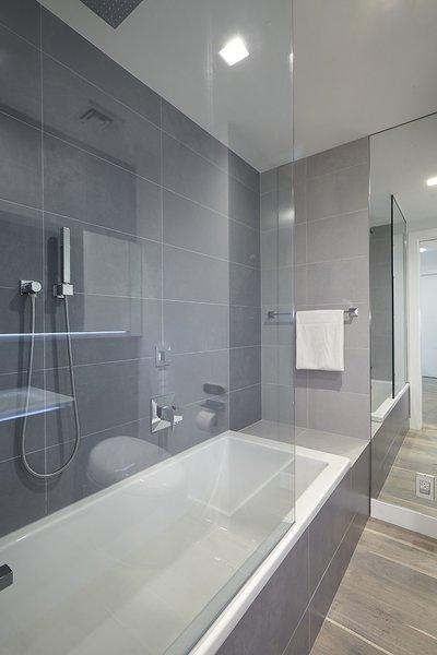 Modern home with bath room, medium hardwood floor, alcove tub, corner shower, soaking tub, ceiling lighting, and porcelain tile wall. Photo 2 of White on White Apartment