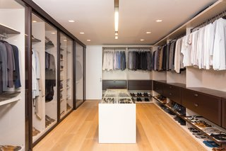 10 Modern Walk-In Closets - Photo 5 of 10 - In this example, clean lines and warm textures create a thoroughly modern design. Glass doors open up the space and extend the open-floor plan.
