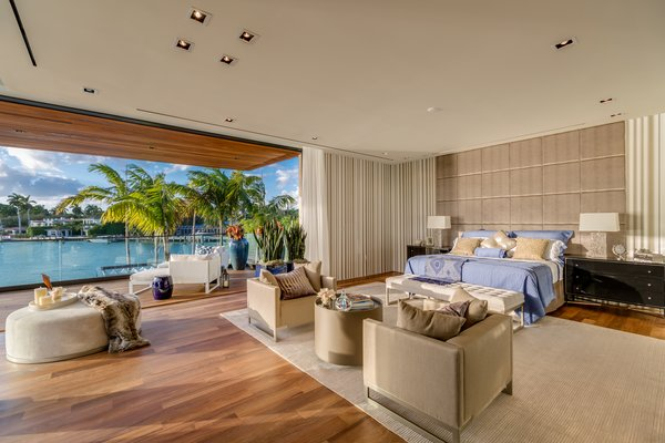 The master bedroom features direct views of the water, and is also designed for indoor-outdoor living. Photo 6 of North Bay Road Residence modern home