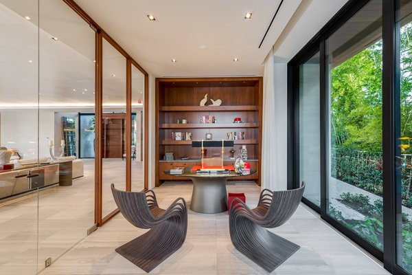 The home's office is adjacent to the living room with views of lush landscape. Photo 8 of North Bay Road Residence modern home