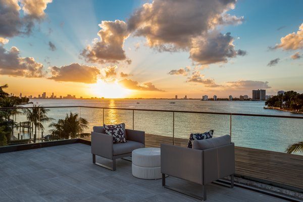 An outdoor seating area on one of the home's many balconies has great views of the sunset. Photo 10 of North Bay Road Residence modern home