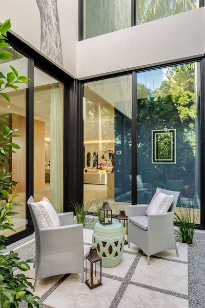 An atrium in the center of the residence allows for a cozy and bright outdoor seating area while still inside the home. Photo 13 of North Bay Road Residence modern home
