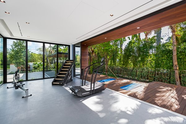 The home's indoor gym makes you feel as if you're outside with its vast pocketing sliding glass doors that open up to a custom yoga deck. Photo 14 of North Bay Road Residence modern home