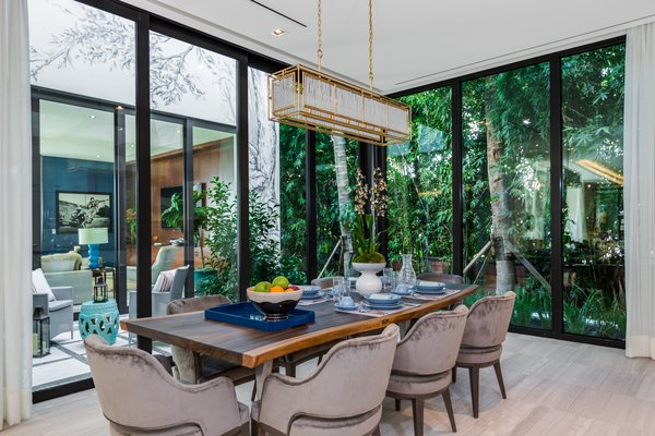 A formal dining room receives natural light from the open atrium and is surrounded by glass on two sides. Photo 15 of North Bay Road Residence modern home