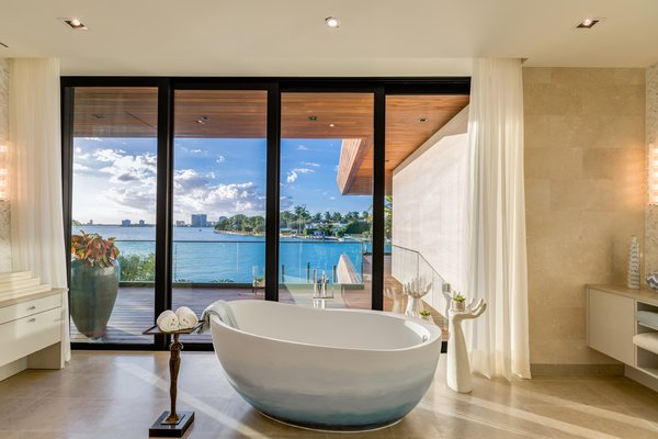 A freestanding tub sits in the center of the master bathroom suite with views of the bay. Photo 16 of North Bay Road Residence modern home