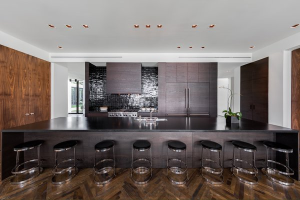 In the kitchen, matte-finish oak cabinetry, a black countertop and black backsplash provide a masculine, monochromatic feel. Photo 4 of Ponce Davis Residence modern home